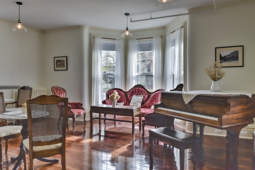 The Slate Room lounge and piano view at The Burrell House Historical Inn Keene, New Hampshire